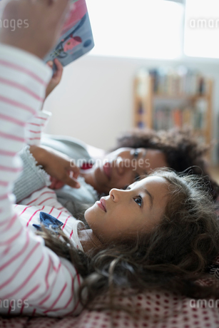 Mother and daughter laying, reading book upside-downの写真素材 [FYI02323086]