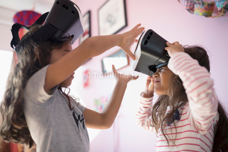 Girl sisters playing with virtual reality simulator glasses in bedroomの写真素材 [FYI02323162]