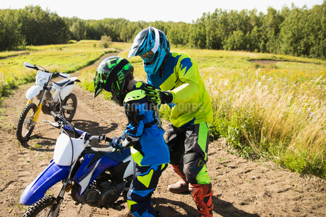 Father helping daughter with motorbike on sunny dirt roadの写真素材 [FYI02323317]