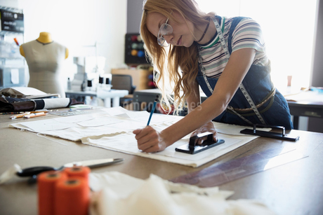 Female fashion designer tracing sewing pattern at workbenchの写真素材 [FYI02323346]