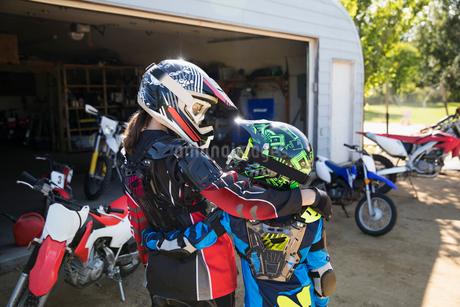 Mother and daughter in motorbike helmets hugging in sunny drivewayの写真素材 [FYI02323349]