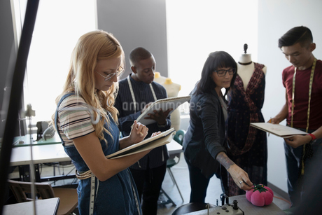 Fashion design instructor and students taking notes and pinning fabric on dressmakers model in studiの写真素材 [FYI02323368]