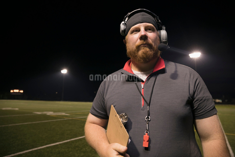 Portrait confident high school football coach with clipboard wearing headset on football field at niの写真素材 [FYI02323419]