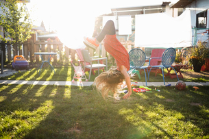 Girl doing handstand in sunny backyardの写真素材 [FYI02323439]