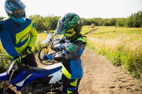 Father helping daughter with motorbike on sunny rural dirt roadの写真素材 [FYI02323448]