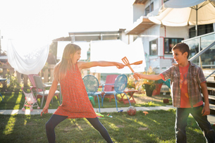 Brother and sister sword fighting with wooden spoons in sunny backyardの写真素材 [FYI02323458]