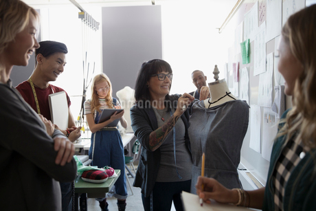 Fashion design students watching instructor pinning fabric on dressmakers model in studioの写真素材 [FYI02323466]
