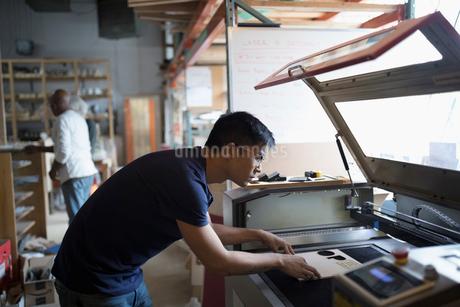 Male engineer using laser cutter in workshopの写真素材 [FYI02323473]