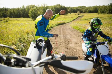 Father with stopwatch timing daughter riding motorbike on rural dirt roadの写真素材 [FYI02323567]
