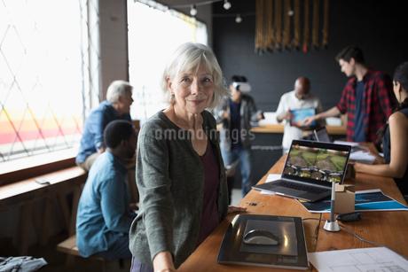 Portrait confident senior female designer at graphics tablet in officeの写真素材 [FYI02323599]