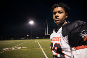 Portrait confident, tough teenage boy high school football player on football field at nightの写真素材 [FYI02323615]