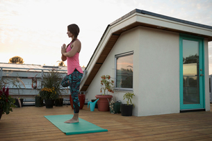 Serene woman standing in yoga tree pose with hands at heart center on yoga mat on deck patioの写真素材 [FYI02323649]