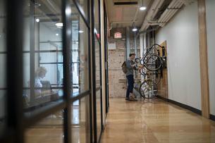 Creative businessman retrieving bicycle from bike rack in office corridorの写真素材 [FYI02323658]