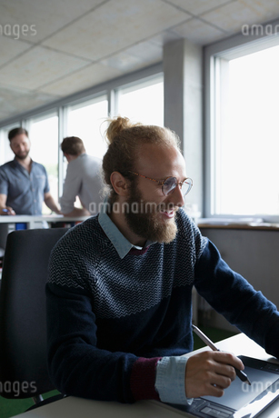 Smiling graphic designer using graphics tablet at office deskの写真素材 [FYI02323680]