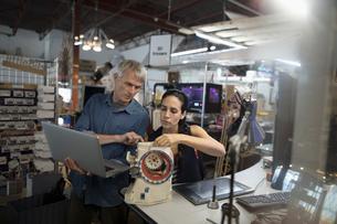Designers with laptop assembling prototype in workshopの写真素材 [FYI02323685]