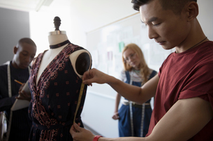 Male fashion design student measuring dress fabric on dressmakers model in studioの写真素材 [FYI02323746]