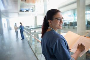 Smiling female nurse reviewing medical record in hospital corridorの写真素材 [FYI02323760]