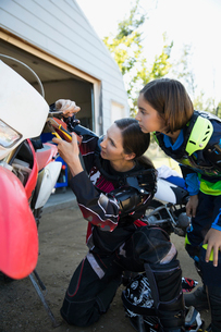 Mother and daughter fixing motorbike in drivewayの写真素材 [FYI02323851]