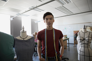 Portrait confident male fashion designer standing among dressmakers model in studioの写真素材 [FYI02323866]