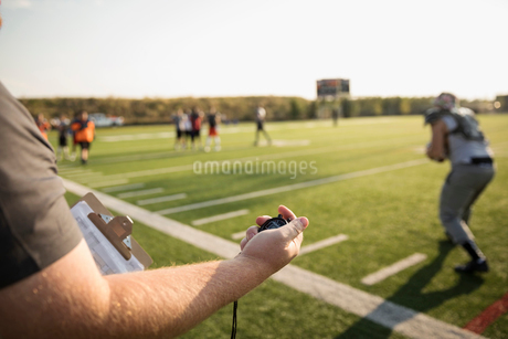 Coach with stopwatch timing teenage boy high school football team running drills on sunny football fの写真素材 [FYI02323872]