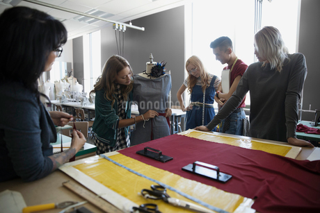 Instructor and fashion design students pinning dress on dressmakers model at workbench in studioの写真素材 [FYI02324096]