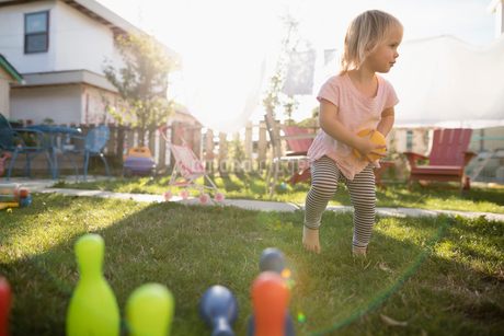 Cute toddler girl playing with bowling toy in grass in sunny backyardの写真素材 [FYI02324188]