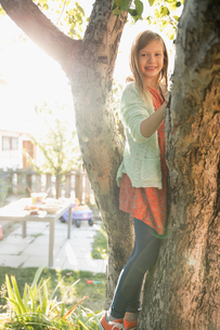 Portrait smiling girl climbing tree in sunny backyardの写真素材 [FYI02324242]