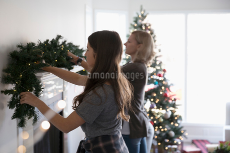 Mother and daughter decorating, hanging garland on fireplace mantle in living roomの写真素材 [FYI02324245]