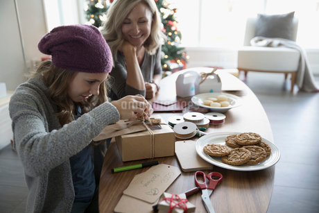 Mother and daughter baking and boxing Christmas cookiesの写真素材 [FYI02324286]