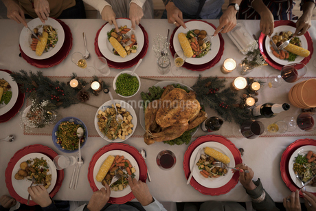 Overhead view family eating candlelight Christmas turkey dinner at tableの写真素材 [FYI02324376]