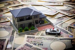 一面の一万円札と家の模型とパトカーの写真素材 [FYI02324386]