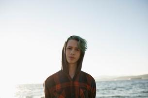 Portrait serious boy with blue hair wearing hoody on ocean beachの写真素材 [FYI02324413]
