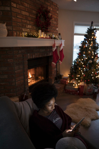Young woman relaxing, using digital tablet near fire and Christmas tree in living roomの写真素材 [FYI02324417]