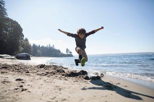 Exuberant boy jumping on sunny ocean beachの写真素材 [FYI02324426]