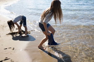 Girl removing rubber boots, wading in sunny ocean beachの写真素材 [FYI02324442]