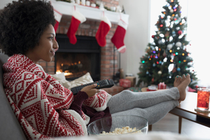 Young woman in pajamas watching TV in Christmas living roomの写真素材 [FYI02324458]