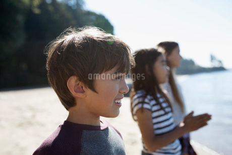 Smiling boy looking away on sunny beachの写真素材 [FYI02324468]