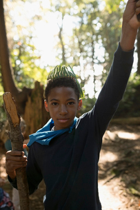 Portrait confident boy with stick and crown in woodsの写真素材 [FYI02324496]