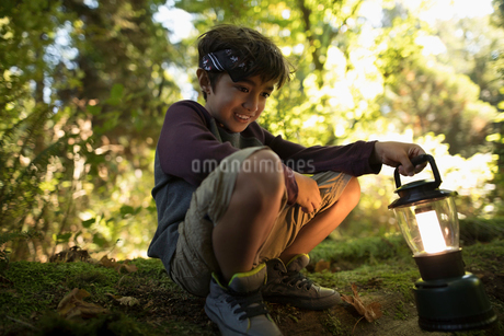 Boy with lantern exploring in woodsの写真素材 [FYI02324501]