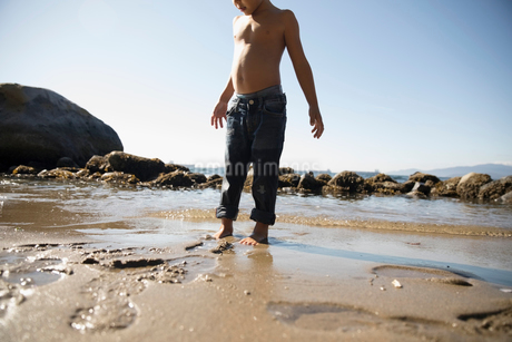 Bare chested boy standing in wet sand on sunny ocean beachの写真素材 [FYI02324585]