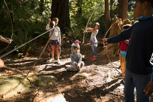 Imaginative boy and girl friends aiming bow and arrows at boy in wolf costume in sunny woodsの写真素材 [FYI02324624]