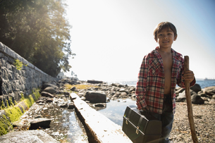 Portrait smiling boy with walking stick and fishing tackle box on sunny beachの写真素材 [FYI02324676]