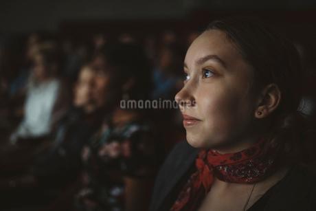 Close up serious tween girl watching movie in dark movie theaterの写真素材 [FYI02324677]