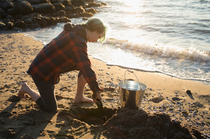 Boy with bucket digging for mussels on sunny ocean beachの写真素材 [FYI02324680]
