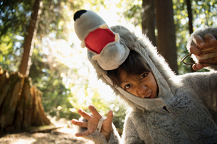 Portrait playful boy in wolf costume gesturing fiercely in woodsの写真素材 [FYI02324692]