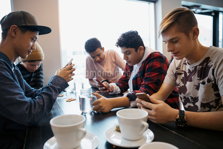 Tween boy friends texting with smart phones and drinking coffee at cafe tableの写真素材 [FYI02324693]