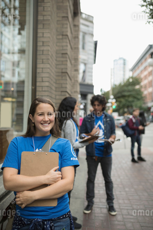 Portrait smiling, confident political young woman canvassing with clipboard on urban sidewalkの写真素材 [FYI02324704]