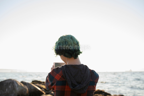 Boy with blue hair photographing ocean with digital tablet cameraの写真素材 [FYI02324710]