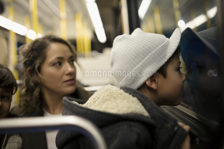 Curious boy riding bus with mother, looking out windowの写真素材 [FYI02324715]