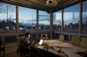 Dedicated father architect working late at laptop with sons playing in conference roomの写真素材 [FYI02324722]